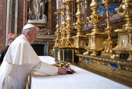"Pope Francis lays flowers at the altar of the Virgin bearing the  icon of the Madonna ""Salus Populi Romani"", or Protectress of the Roman People."