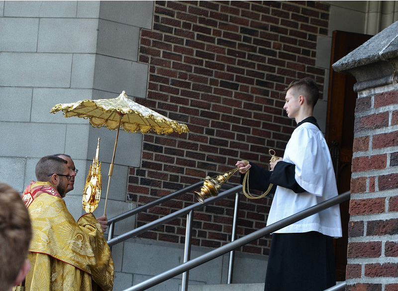 Fr. Wichert holds the ombrellino over Fr. Stinson, who carries our Eucharistic Lord (photo by Emily Gossard)