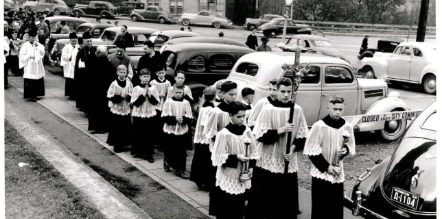 Holy Rosary parish celebrated its 50th anniversary on Oct. 19, 1941, with a processional led by altar boys exhibiting varying degrees of piety and including the Bishop of Seattle, Gerald Shaughnessy. The young cross-bearer is Daniel Jacques, and the acolytes on either side are Robert Beaudean and George Bader.